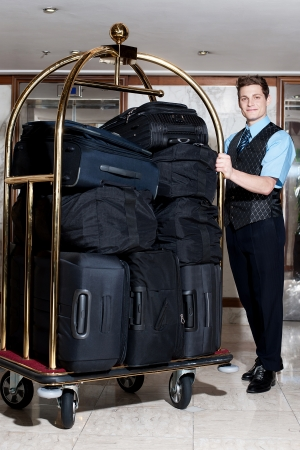 Photo pour Handsome male concierge posing with a pile of bags in luggage cart - image libre de droit