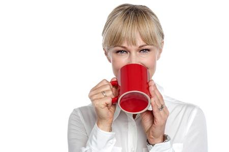 Attractive employee enjoying her coffee break,looking at the camera.