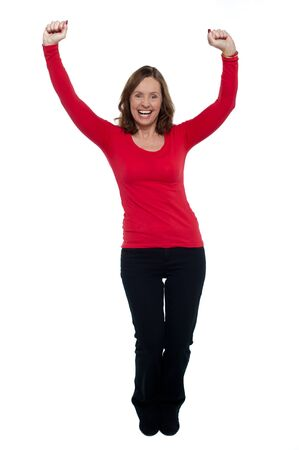 Jubilant lady celebrating her success, throwing up her hands in the air, full length.