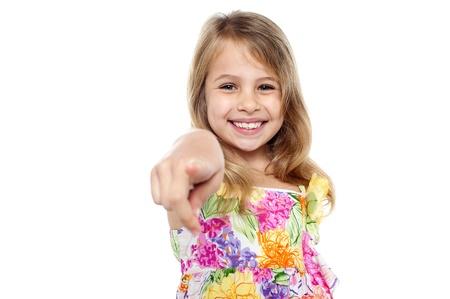 Photo pour Cute little smiling blonde girl pointing finger towards the camera. - image libre de droit