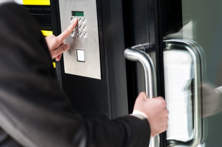 Businessman entering safe code to unlock the door