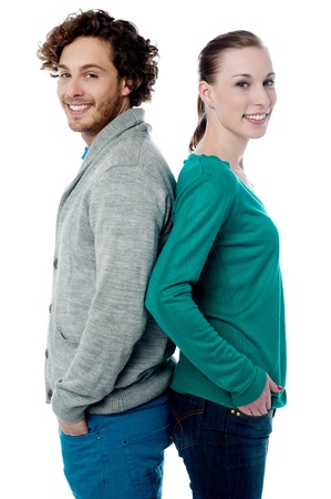 Trendy young smiling couple posing back to back