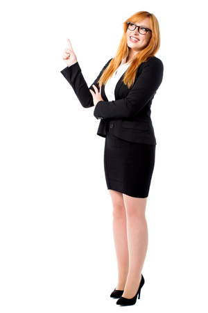 Young female executive pointing and looking upwards