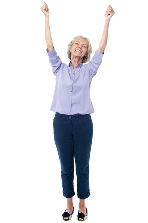Excited senior citizen raising her hands