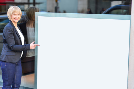 Business woman pointing at blank whiteboard