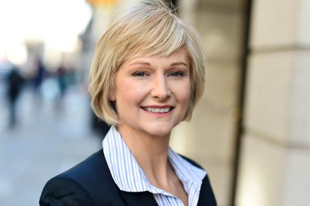 Photo pour Smiling middle aged woman standing outside the office - image libre de droit