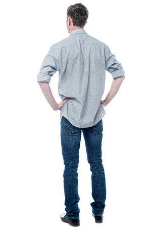 Back pose, full length shot of a young man looks ahead