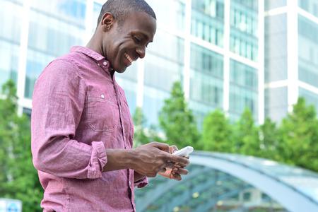 Photo pour Handsome african man texting to his friend - image libre de droit