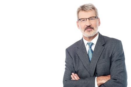 Smiling aged businessman posing with crossed arms