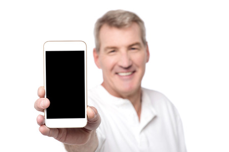 Happy senior man showing his mobile to camera