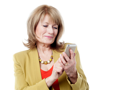 Photo for Mature woman dialing on a smart phone - Royalty Free Image
