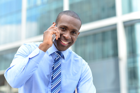 Happy male executive speaking using cell phone