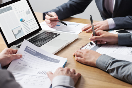 Business professionals working together at office desk, hands close up pointing out financial data on a report, teamwork concept