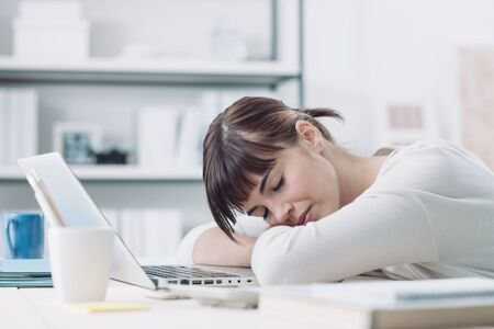 Young tired woman at office desk sleeping with eyes closed, sleep deprivation and stressful life concept