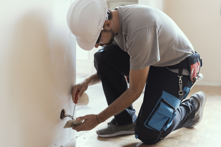 Photo pour Professional electrician installing sockets using a screwdriver: home renovation and maintenance concept - image libre de droit