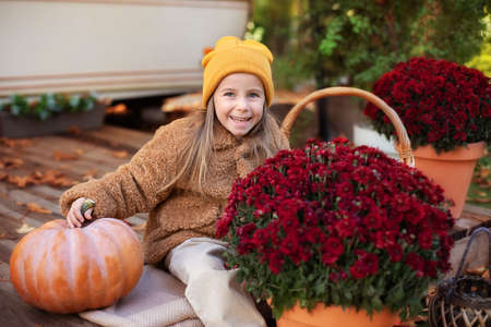 Foto de Happy little girl sitting on porch of house with chrysanthemums potted and pumpkins. home fall decoration for Halloween or Thanksgiving. Smilling Child in autumn garden with yellow pumpkins and flower - Imagen libre de derechos