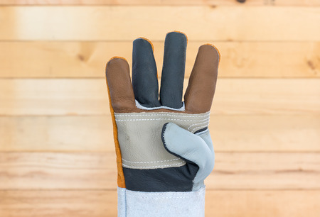Working hand in Rough leather glove with wall wood background