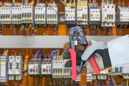 Hand in rough leather glove holding a wire stripper tool with control panel cabinet background