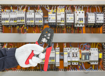 Hand in glove holding a wire stripper tool with control panel cabinet background