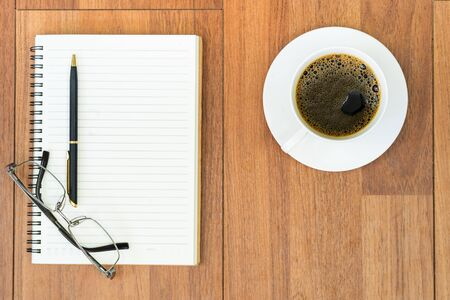 Photo for Top view eyeglasse and pen on notepad and coffee cup on wood deck with copy space - Royalty Free Image