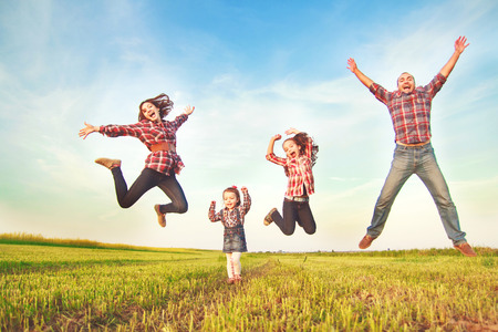 Photo pour family jumping together in the field - image libre de droit