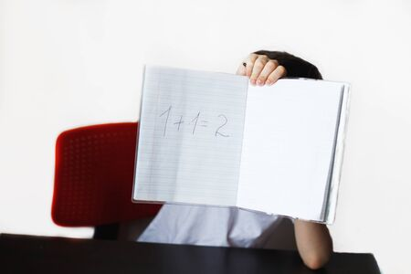 Photo pour the child is studying.the child decided an example . child sits and does homework on a white background - image libre de droit