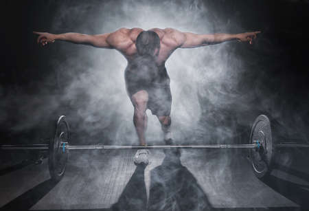 Photo pour very power athletic guy standing with barbell, workout in the gym - image libre de droit
