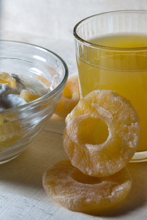 Breakfast with Yogurt with pieces of pineapple and orange juice on a wooden background