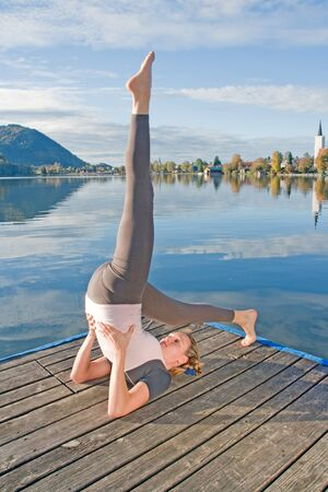 Young woman doing yoga by the lake