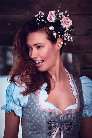Portrait of a young, smiling woman in a dirndl with flowers in her hair.