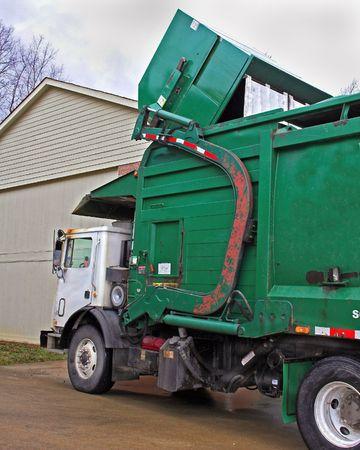 Truck pickingup dumpster full of trash