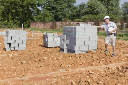 Building inspector checking block walls, building framing,electrical and plumbing stubouts