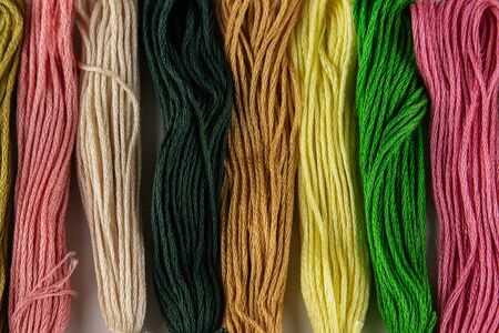 Photo pour Seven skeins of colored thread for embroidery lie on a table in a row. They are arranged vertically. The colors are pink, green, yellow and their shades. Photo close-up. - image libre de droit