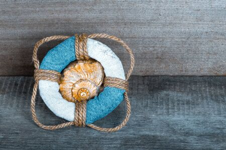 Lifebuoy on old grey wooden background in sea style with wood, denim and rope material.