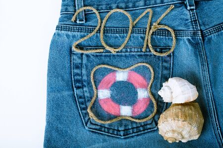 Lifebuoy, rope number 2016 and seashell on jeans pocket background.