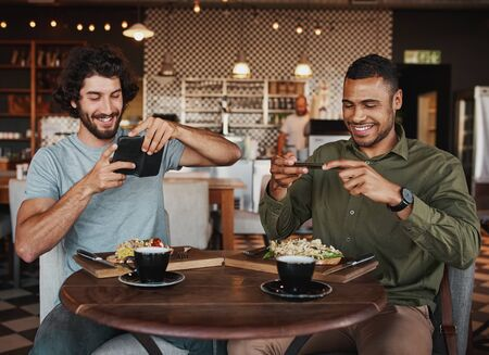 Young afro-american and caucasian male friends clicking photo of italian bruschetta with coffee in cafe while enjoying lunch