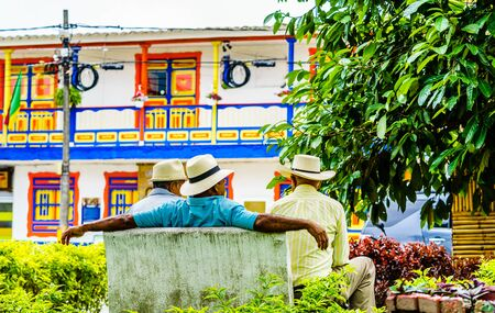 Photo pour View on people of Colombia, group of old man sitting on bench in the colorful streets of Filandia Village - image libre de droit