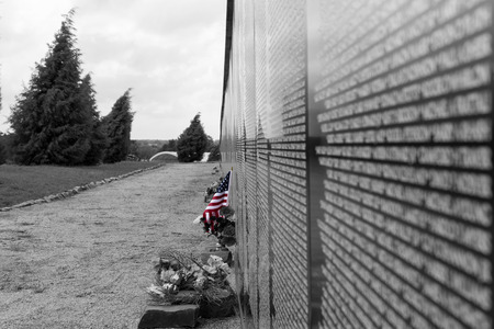 US Flag placed to honor a name at a Vietnam War Memorial Wall on a cloudy overcast day