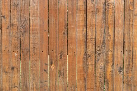 Photo pour Pattern of stained, reddish brown wood slats of a privacy fence that show signs of fading and stains after having been aged and weathered by the elements and weather over time. - image libre de droit