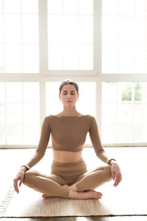Foto für Young slim elegant woman in beige sportswear is sitting on a natural rug on the floor with closed eyes, resting and relaxing after training, front view with window background.Wellness, harmony concept - Lizenzfreies Bild