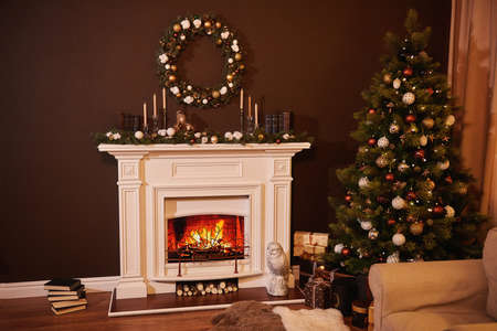 Foto de Christmas tree with beautiful balls in a cozy brown living room with a fireplase. Christmas room interior design, Xmas tree decorated by lights, candles and garland lighting indoors fireplace - Imagen libre de derechos
