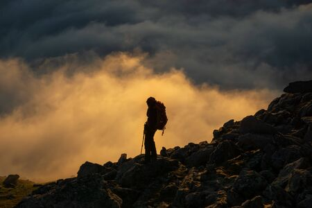 Photo pour Hiker on Breidtinden with clouds in background at sunset, Senja, Norway - image libre de droit