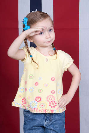 Foto per Cute girl saluting with a patriotic design in the background - Immagine Royalty Free