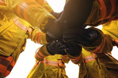 Foto de Firefighter putting hands up for fire fighting, Cheerful people giving strength motivation. Teamwork concept - Imagen libre de derechos