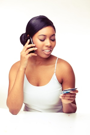 african woman speaking over the phone , paying using  credit card