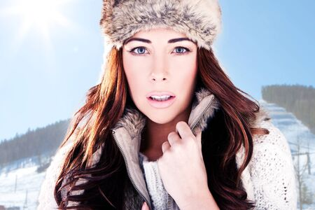 Winter Woman On Ski Slope. Close-up headshot of a beautiful woman dressed in winter fur with a mountain ski slope background