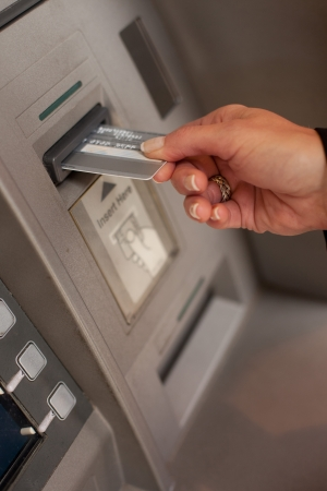 Photo pour Female hand inserting a bank card at an automatic bank teller machine to withdraw or deposit money - image libre de droit