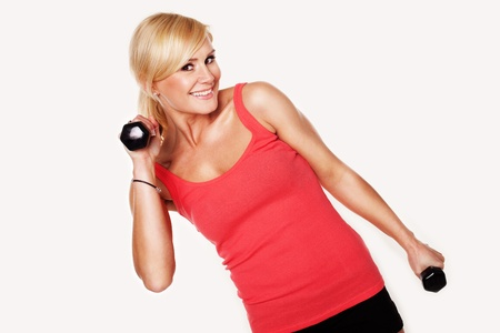 Fit smiling blonde woman in shorts lifting a pair of dumbbells to shoulder height as she exercises and works out, isolated on white
