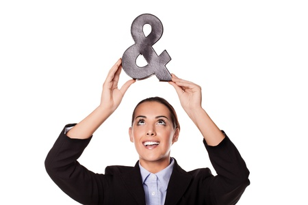 Beautiful smiling happy businesswoman holding up an ampersand sign symbolic of a new business partner or partnership isolated on white
