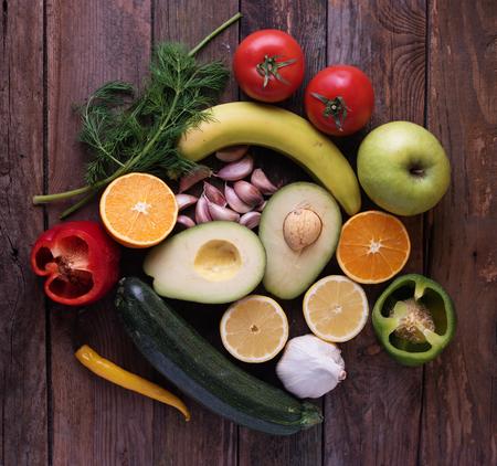 Foto für fruits and vegetables on wooden board including fresh avocado, garlic,  orange and apple - Lizenzfreies Bild